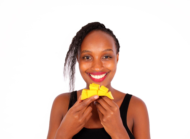 Smiling woman eating sliced mango