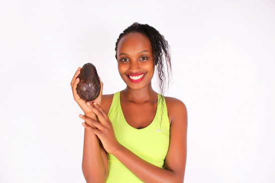 Smiling woman holding black avocado