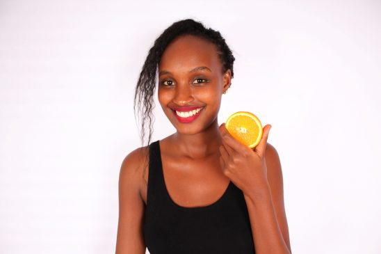 Smiling woman holding sliced orange