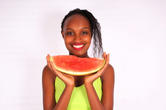 Smiling woman holding watermelon fruit