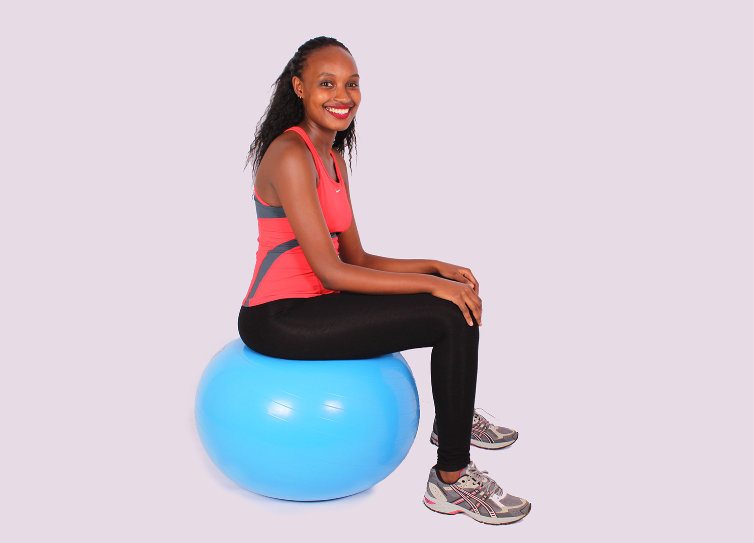 Smiling woman sitting on swiss ball ready to exercise