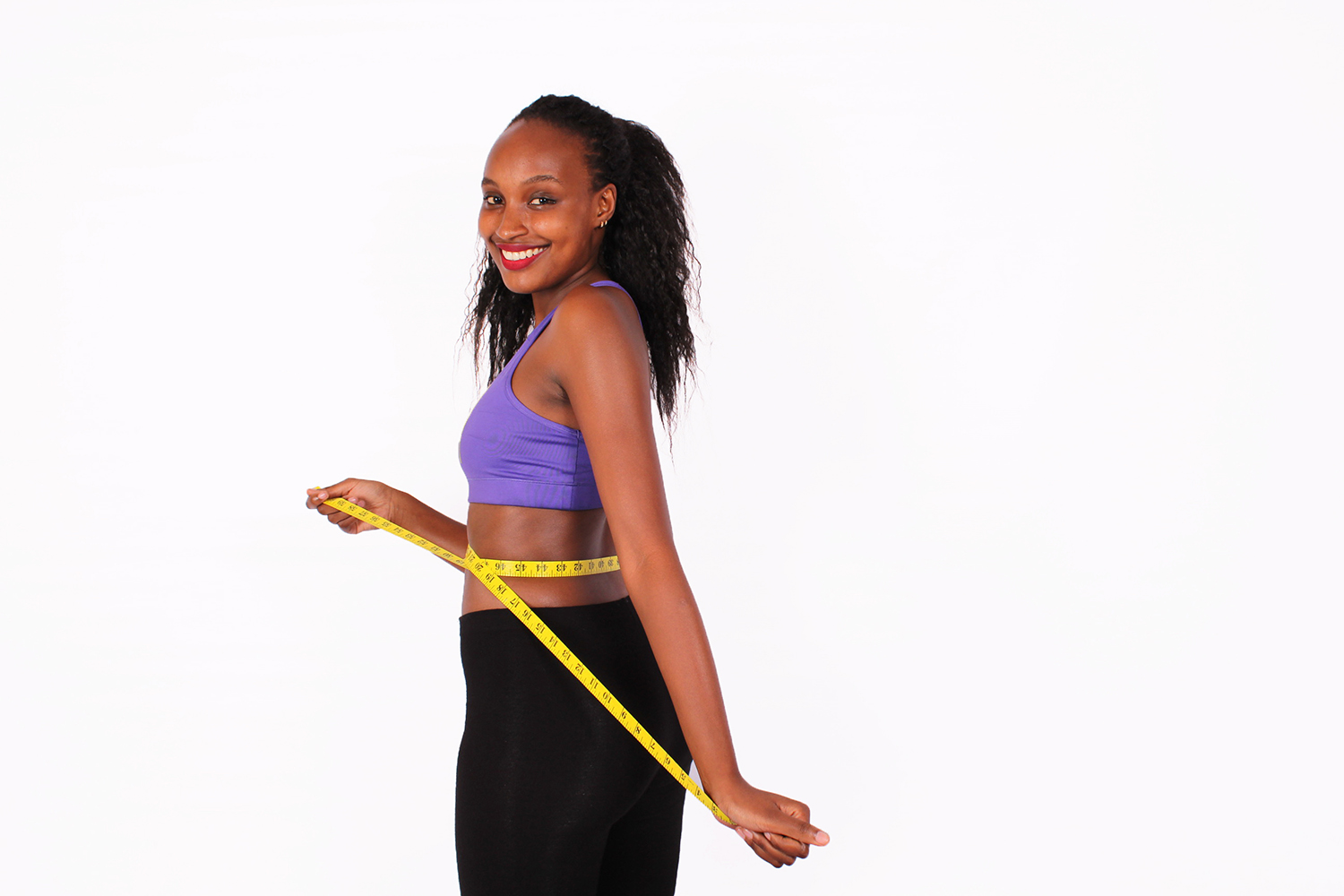 Sporty woman measuring waist size with tape measure