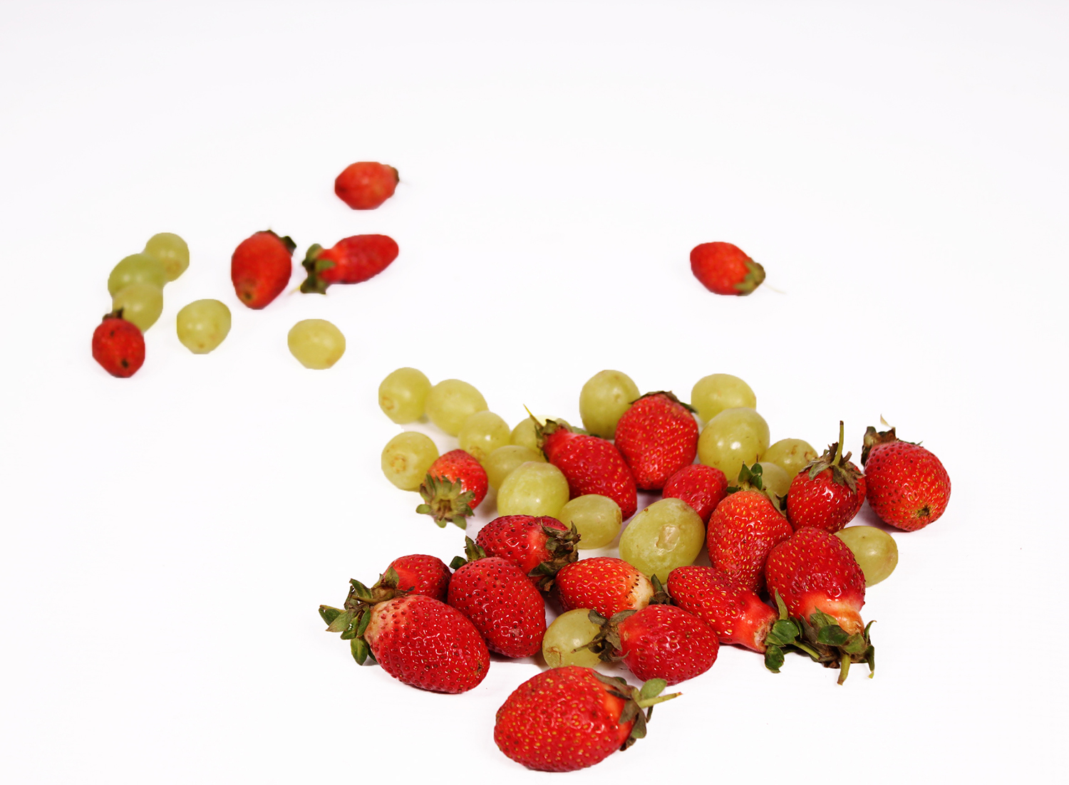 Strawberries and green grapes on white background