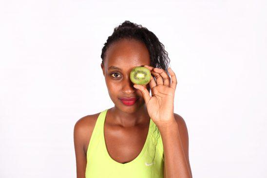 Woman covering eye cut kiwi fruit