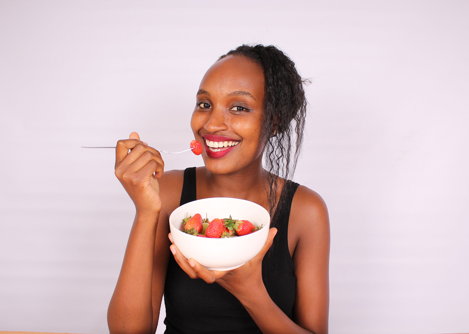 Woman eating fresh strawberries using a folk