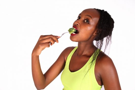 Woman eating raw broccoli with folk