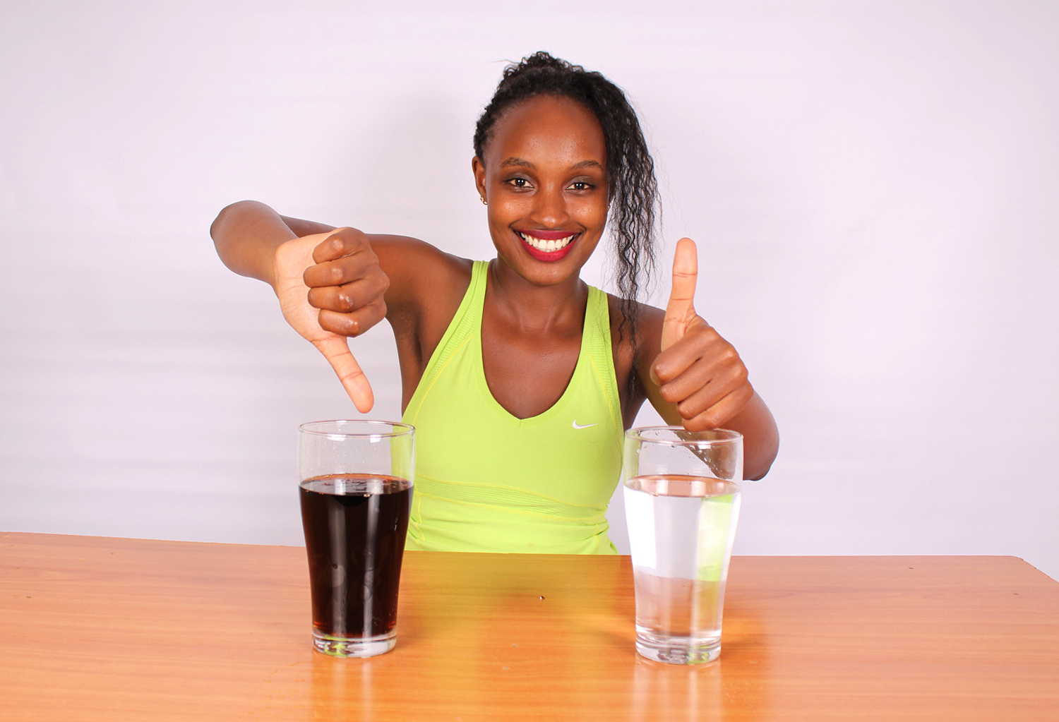 Soda vs Water. Woman gives thumps up water and thumbs down for soda