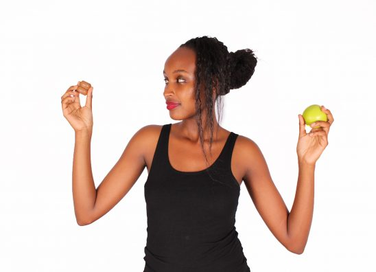 Woman holding piece of chocolate and green apple