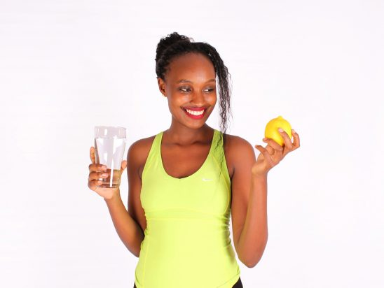 Woman holding water glass and yellow lemon