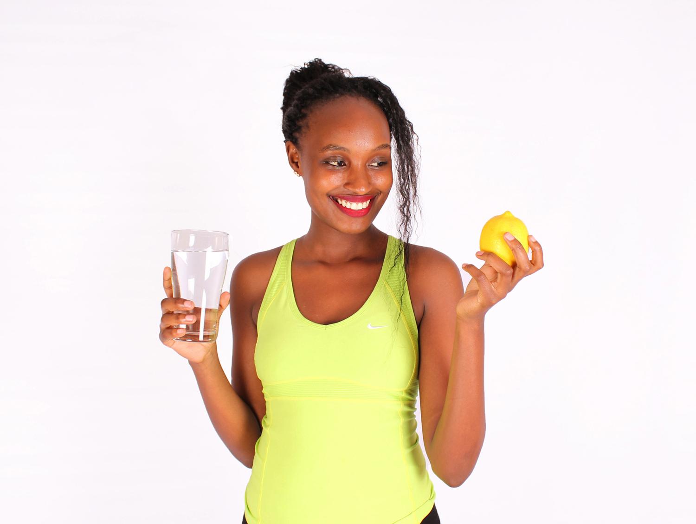 Woman holding water glass and yellow lemon