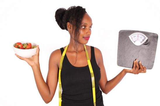Woman holding weight scale and bowl of fruits