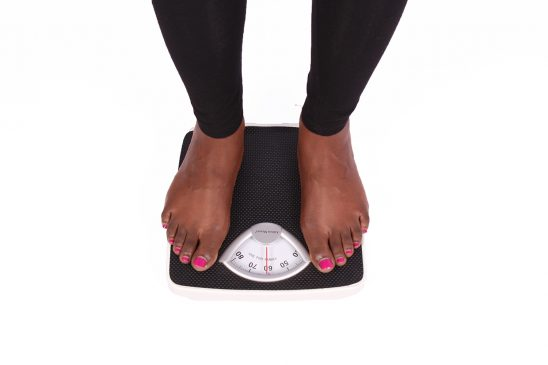 Woman legs stepping on weighing scale