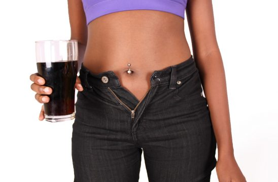 Woman waistline expanding after drinking soda
