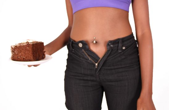Woman waistline expanding after eating cake