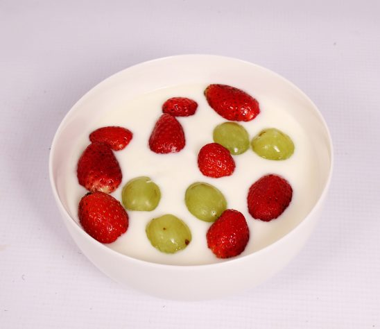 Yogurt with strawberries and green grapes toppings