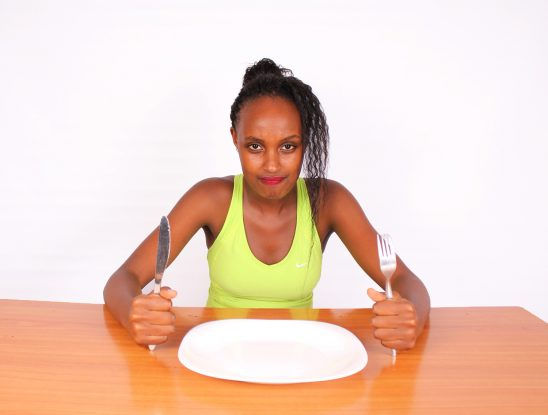Young woman frustrated with dieting table with empty plate