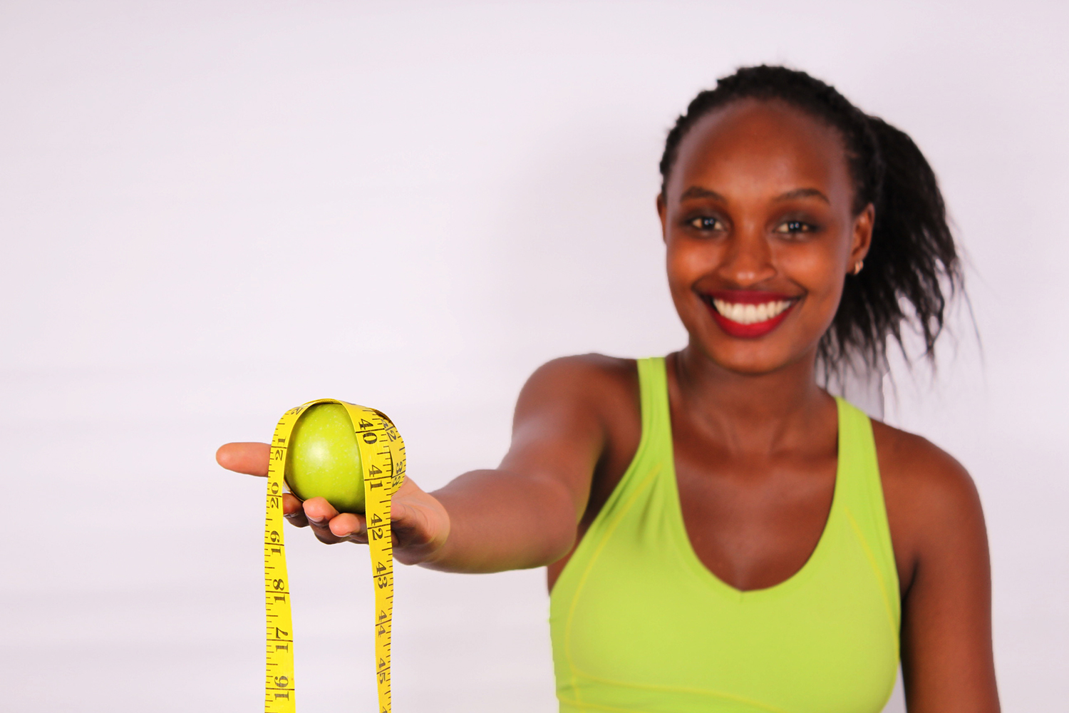 Young woman holding apple wrapped with tape measure