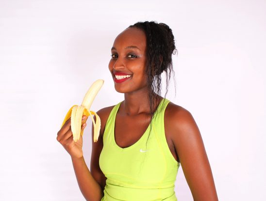Young woman holding peeled banana