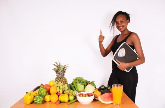 Young woman holding weigh scale gives thumbs up for fruits and vegetables